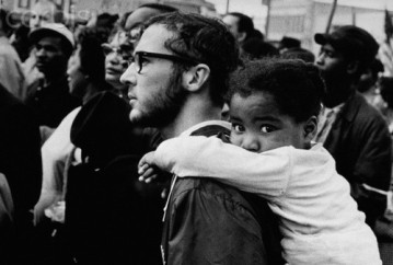 ca. 1965, Selma, Alabama, USA --- A white man carries a black girl on his shoulders during a march with Dr. Martin Luther King, Jr. Alabama, ca. 1965. --- Image by © Carl & Ann Purcell/CORBIS